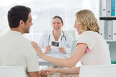 Expectant couple with doctor in clinic — Stock Photo