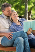 Affectionate couple reading book — Stock Photo