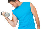 Fit young man exercising with dumbbell — Stockfoto