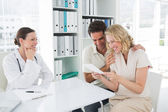 Expectant couple looking at reports in clinic — Stock Photo