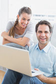Happy couple using laptop smiling at camera — Stock Photo