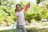 Girl holding kite at park — Stock Photo
