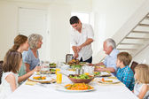 Father serving meal to family — Stock Photo