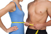 Mid section of a fit man measuring womans waist — Stock Photo