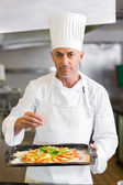 Confident chef holding cooked food in kitchen — Stock Photo