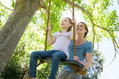Happy mother swinging daughter at park — Stock Photo