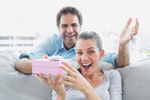 Man surprising his delighted girlfriend with a pink gift on the sofa — Stok fotoğraf