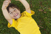 Young boy lying on grass at park — Foto Stock
