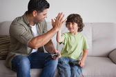 Father and son playing video games in living room — Stock Photo