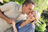 Romantic man kissing woman in park — Stock Photo