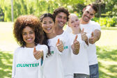 Confident volunteers gesturing thumbs up — Stock Photo