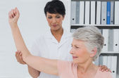 Physiotherapist assisting senior woman to stretch her hand — Foto Stock