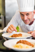 Closeup portrait of a male chef garnishing food — Stock Photo