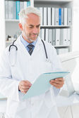 Doctor looking at a folder in the medical office — Stock Photo