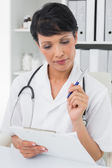 Concentrated female doctor writing on clipboard — Stock Photo