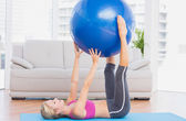 Blonde holding exercise ball between legs — Stock Photo