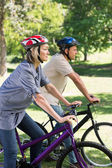 Couple riding bicycles in park — Stock Photo