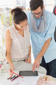 Fashion designers using digital tablet in studio — Fotografia Stock