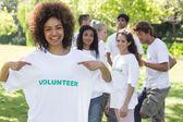 Volunteer pointing at tshirt — Stock Photo