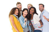 Happy group of young friends having fun doing karaoke — Stock Photo