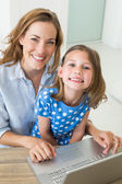 Girl with mother using laptop — Stock Photo