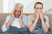 Sick couple sitting on the couch under a blanket — Stock Photo