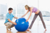 Pregnant woman exercising with trainer — Stock Photo