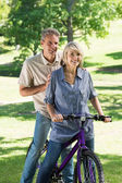 Couple riding bicycle in park — Stock Photo