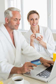Smiling couple using laptop at breakfast in bathrobes — Foto de Stock