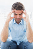Wincing man with headache sitting on the couch — Stock Photo