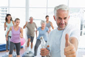 Senior man gesturing thumbs up with people exercising in fitness studio — Stock Photo
