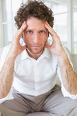 Worried well dressed man sitting with head in hands — Stock Photo