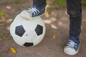 Low section of boy with leg on football at park — Stock Photo