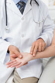 Mid section of a doctor taking a patients pulse — Stock Photo