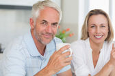 Happy couple having coffee together looking at camera — Stock Photo