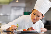 Concentrated female chef garnishing food in kitchen — Stock Photo