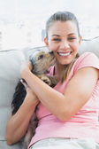 Pretty woman cuddling her yorkshire terrier on the couch — Stock Photo