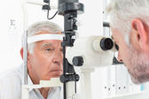 Optometrist doing sight testing for senior patient — 图库照片