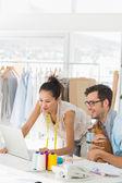 Fashion designers using laptop in studio — Foto de Stock