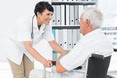 Doctora hablando con un paciente senior en silla de ruedas — Foto de Stock