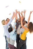 Happy group of young friends throwing money in the air — Stock Photo