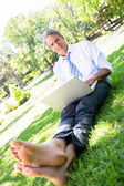 Businessman with laptop sitting on parkland — Stock Photo