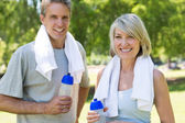 Couple holding water bottles in the park — Stock Photo