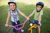 Siblings riding bicycles — Stock Photo