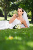 Bride blowing a kiss in park — Stock Photo