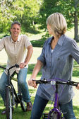 Loving couple riding bicycles in park — Stock Photo