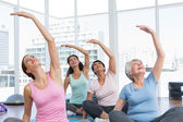 Class stretching hands at yoga class — Stock Photo
