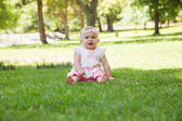 Happy cute baby sitting on grass at park — Stock Photo