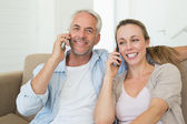 Happy couple sitting on couch talking on their phones — Stock Photo