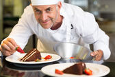 Smiling male pastry chef decorating dessert in kitchen — Stock Photo